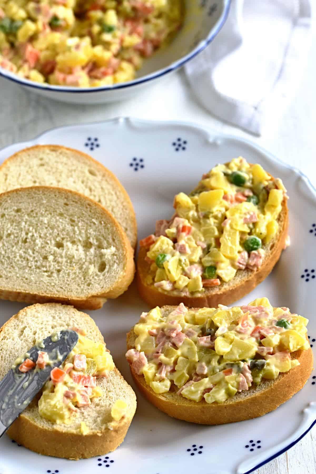 spreading vlašský salát on white bread