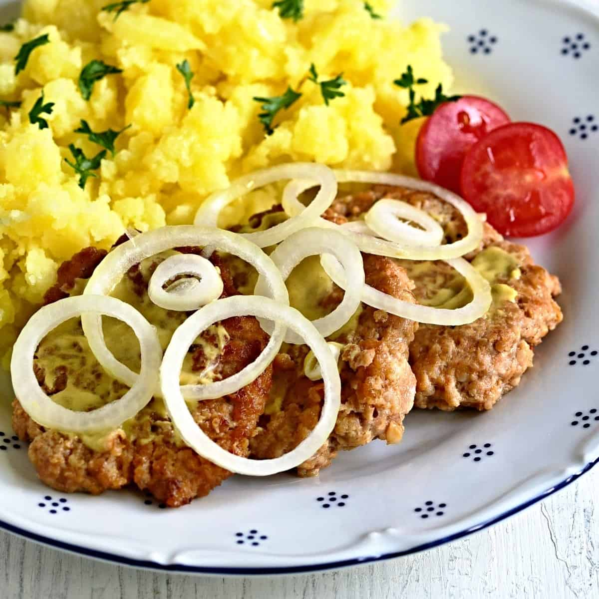 pork patties served with onion circles and potatoes
