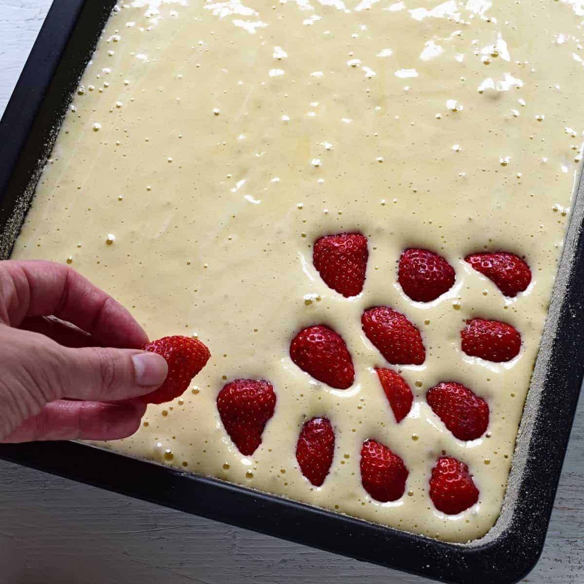 putting strawberries on a batter