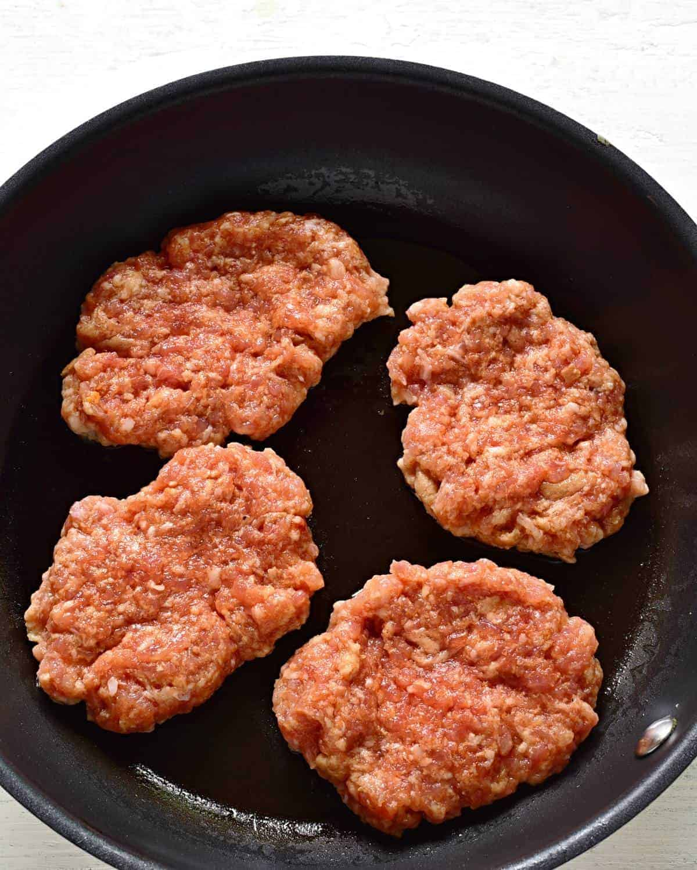 frying pork patties in a pan