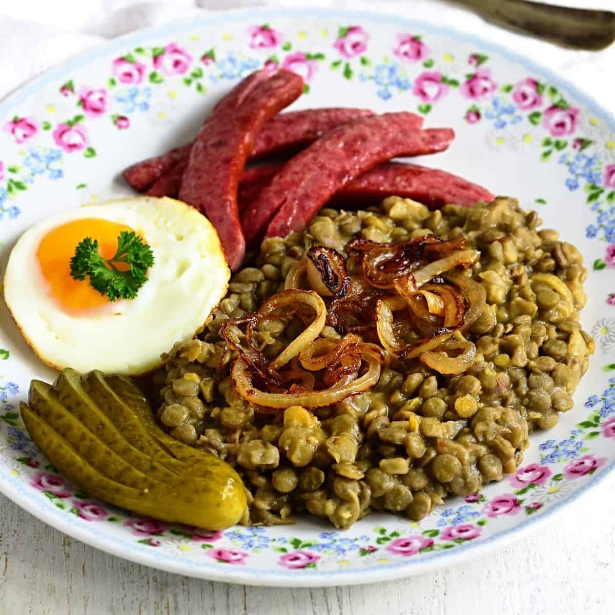 Czech dish čočka na kyselo served with fried egg, sausage, pickles.