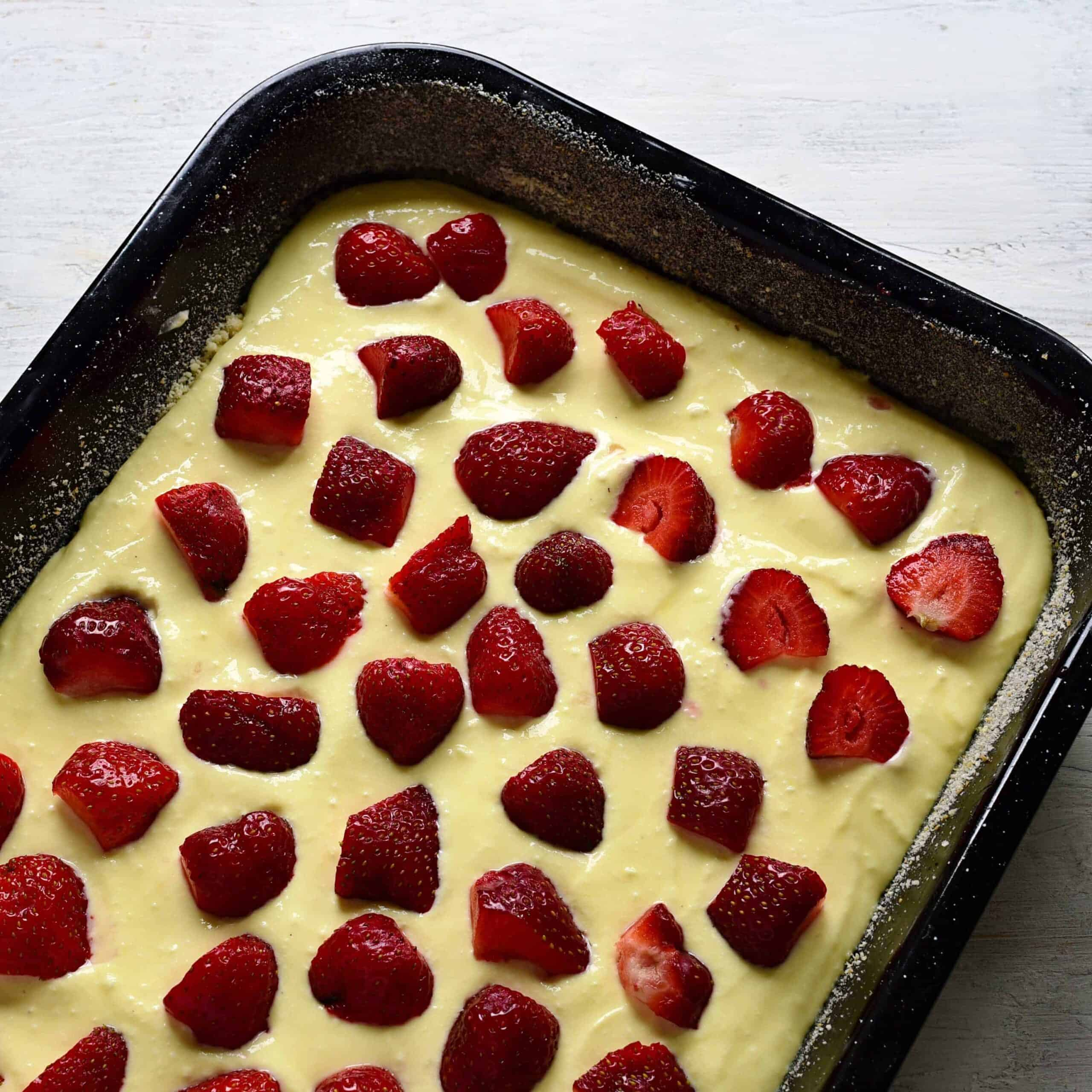 putting strawberries over cream cheese filling