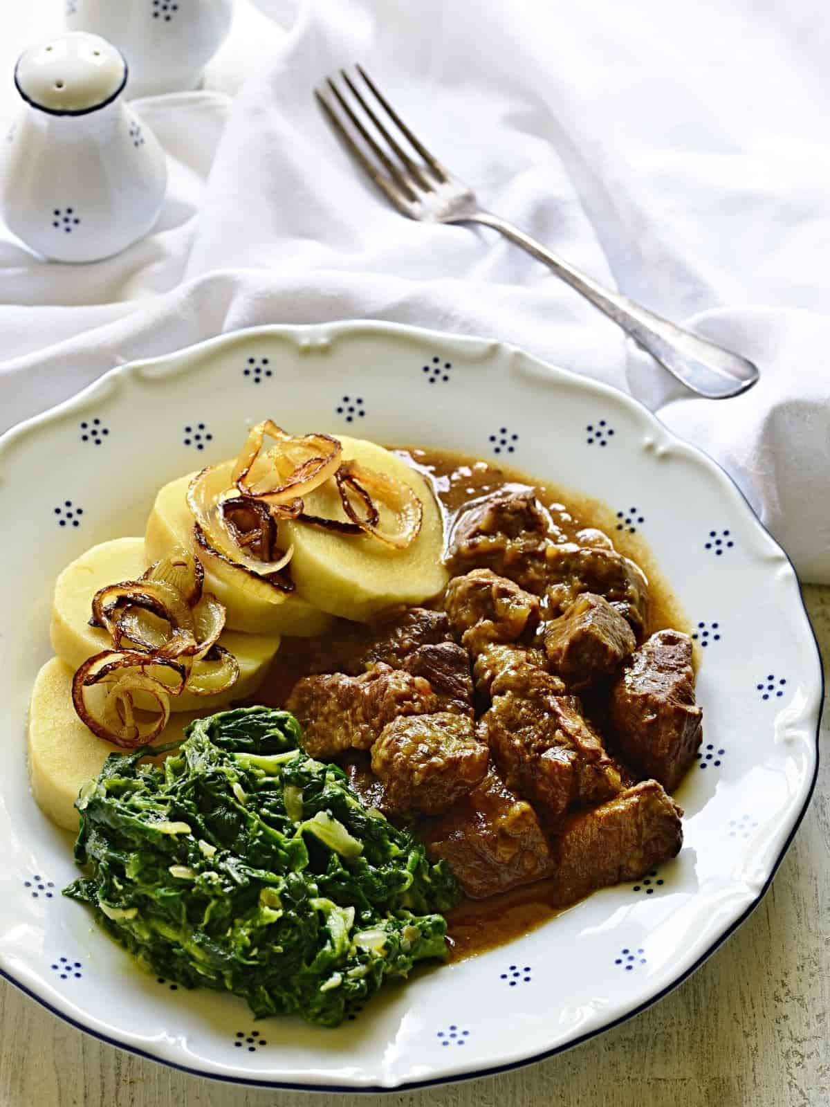 Beef cubes with garlic gravy, served with potato dumplings and spinach.