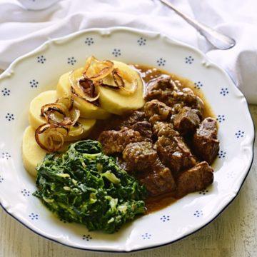 Garlic beef cubes served with potato dumplings and spinach, Czech hovězí na česneku dish.