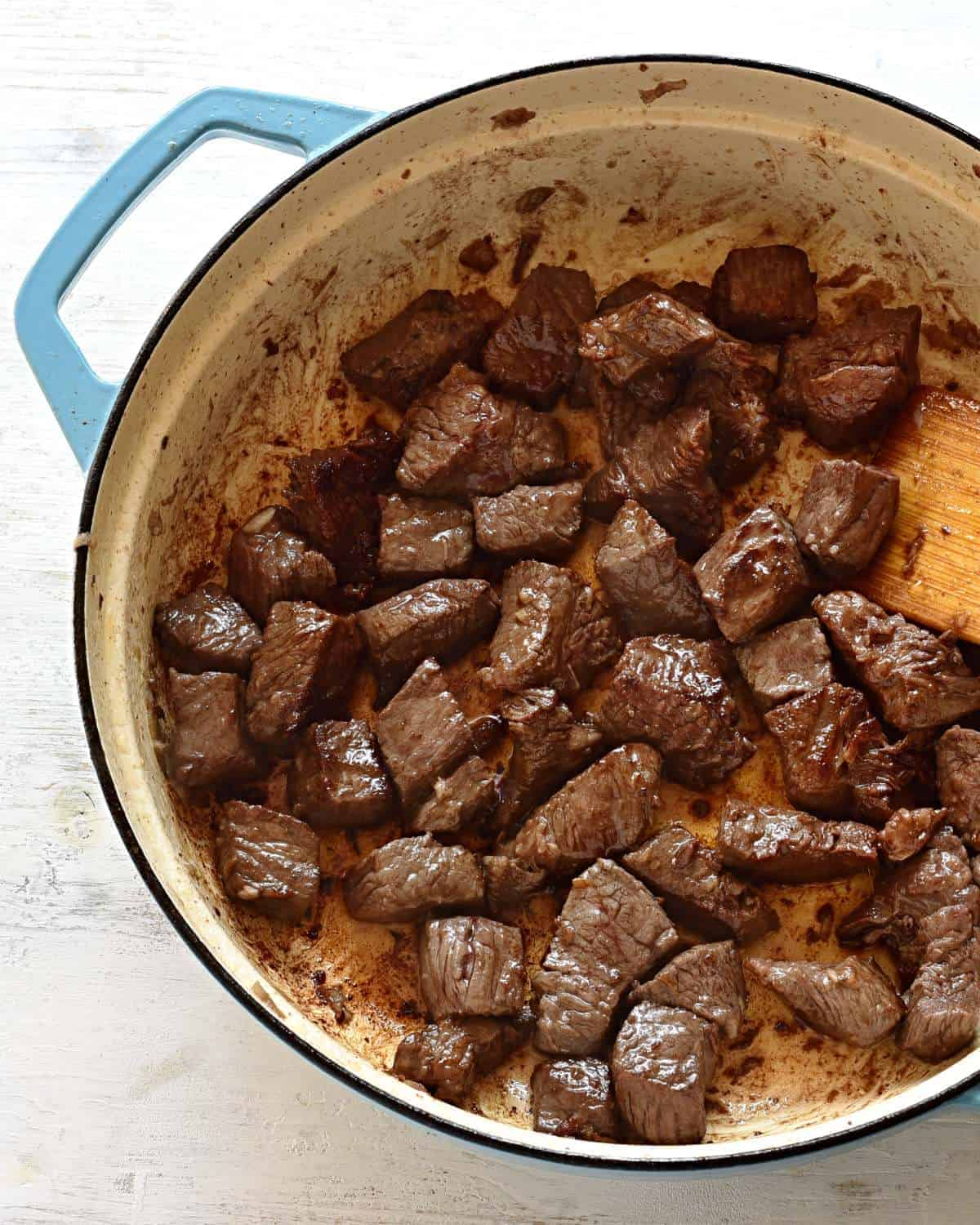 Searing beef cubes in a pan.